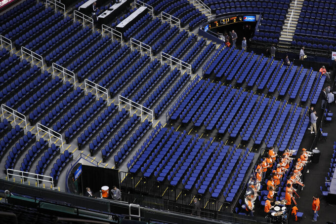 The Clemson band sits in a mostly empty Greensboro Coliseum after the NCAA college basketball games were cancelled at the Atlantic Coast Conference tournament in Greensboro, N.C., Thursday, March 12, 2020. The biggest conferences in college sports all canceled their basketball tournaments because of the new coronavirus, seemingly putting the NCAA Tournament in doubt.(AP Photo/Gerry Broome)