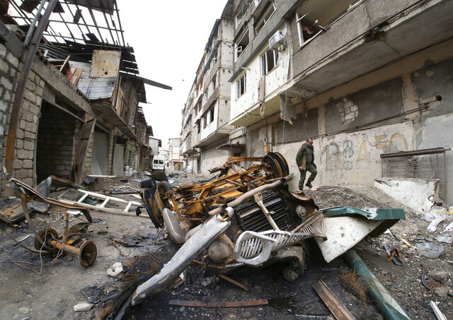 A man walks in the yard of an apartment building damaged by shelling by Azerbaijan's artillery during a military conflict in Stepanakert, self-proclaimed Republic of Nagorno-Karabakh, Wednesday, Oct. 7, 2020. Armenia accused Azerbaijan of firing missiles into the capital of the separatist territory of Nagorno-Karabakh, while Azerbaijan said several of its towns and its second-largest city were attacked. (AP Photo/Dmitri Lovetsky)