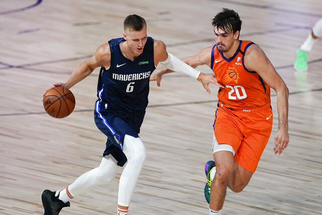 Dallas Mavericks forward Kristaps Porzingis (6) drives against Phoenix Suns forward Dario Saric (20) during the first half of an NBA basketball game Sunday, Aug. 2, 2020, in Lake Buena Vista, Fla. Porzingis will miss the start of the season as the Mavericks star continues recovery from surgery to repair a torn meniscus in his right knee. Director of basketball operations Donnie Nelson said in a radio interview Monday, Nov. 16, 2020, the club was being cautious with Luka Doncic's European sidekick, who missed more than a season because of another knee injury.(AP Photo/Ashley Landis, Pool)