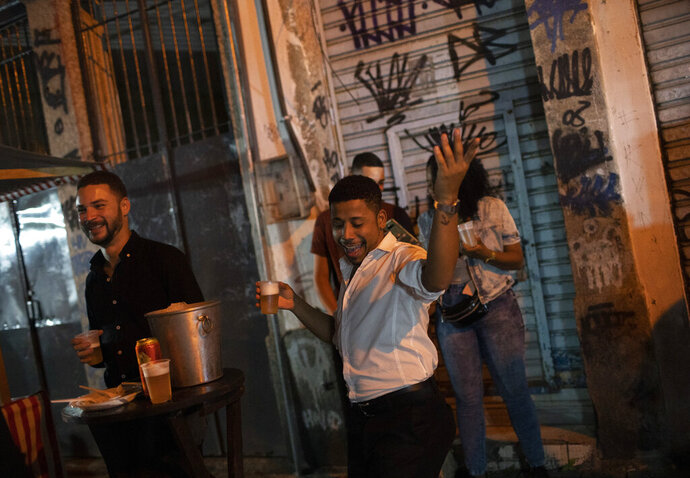 A man dances during a street performance by the Brazilian band Atitude Nossa as the restrictions related to the COVID-19 pandemic are eased in Rio de Janeiro, Brazil, Monday, Oct. 5, 2020. Since the beginning of October, live shows are now permitted in Rio de Janeiro. (AP Photo/Silvia Izquierdo)