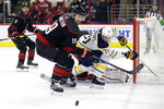 Carolina Hurricanes' Dougie Hamilton (19) and Buffalo Sabres' Evan Rodrigues (71) struggle for possession of the puck during the first period of an NHL hockey game in Raleigh, N.C., Friday, Jan. 11, 2019. (AP Photo/Gerry Broome)