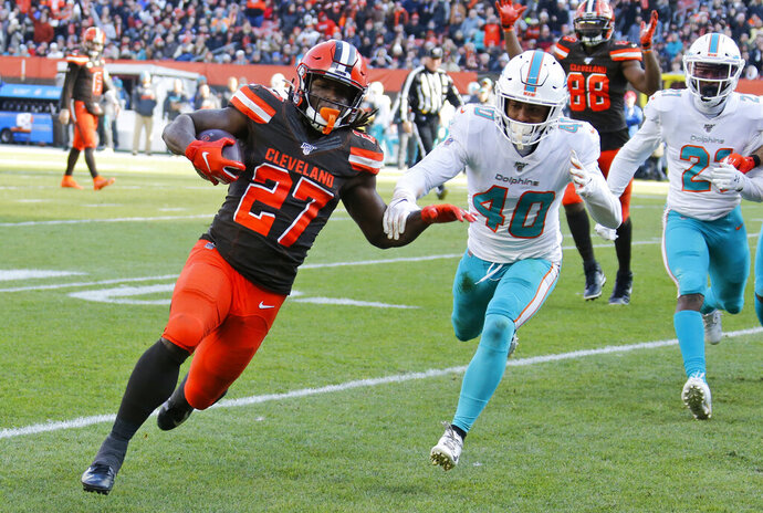 Cleveland Browns running back Kareem Hunt (27) scores a 6-yard touchdown during the first half of an NFL football game against Miami Dolphins defensive back Nik Needham (40), Sunday, Nov. 24, 2019, in Cleveland. (AP Photo/Ron Schwane)