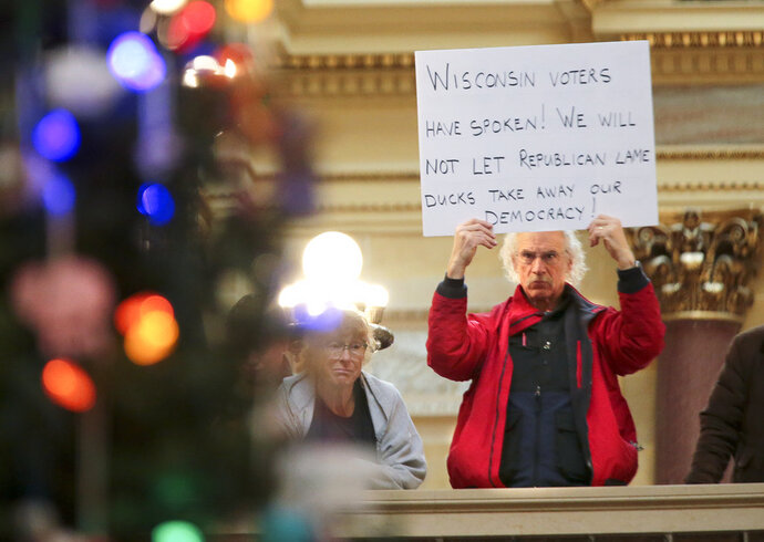 Bob Kinosian, from Wauwatosa, Wis., holds up a sign during the state Christmas Tree lighting ceremony in state Capitol Rotunda Tuesday Dec. 4, 2018, in Madison, Wis. The Senate and Assembly are set to send dozens of changes in state law to Gov. Scott Walker's desk. (Steve Apps