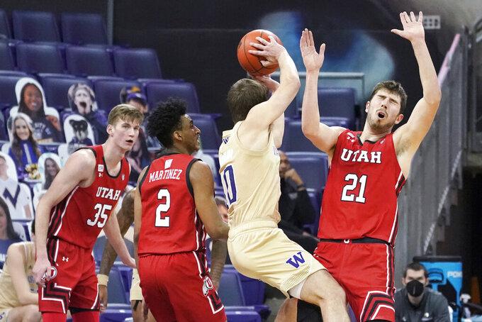 Utah forward Riley Battin (21) reacts as Washington guard Erik Stevenson (10) grabs a rebound during the second half of an NCAA college basketball game, Sunday, Jan. 24, 2021, in Seattle. Washington won 83-79. (AP Photo/Ted S. Warren)