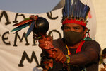 """An Indigenous man performs a ritual during the """"Luta pela Vida,"""" or Struggle for Life mobilization, a protest to pressure Supreme Court justices who are expected to issue a ruling that will have far-reaching implications for tribal land rights, outside the Supreme Court in Brasilia, Brazil, Wednesday, Aug. 25, 2021. (AP Photo/Eraldo Peres)"""