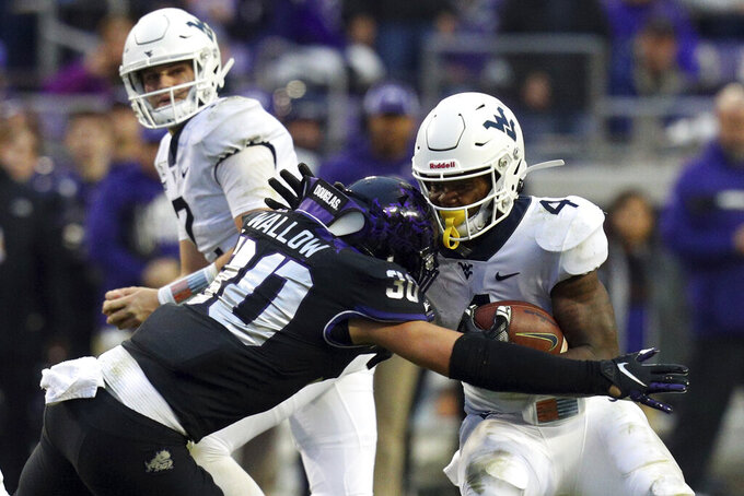 FILE - In this Nov. 29, 2019, file photo, TCU linebacker Garret Wallow (30) tackles West Virginia running back Leddie Brown (4) in an NCAA college football game, in Fort Worth, Texas. Wallow was selected to The Associated Press All-Big 12 Conference team, Friday, Dec. 13, 2019. (AP Photo/Richard W. Rodriguez, File)
