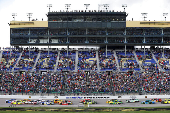 Fans watch from the grandstand as race cars cross the start/finish line at the start of a NASCAR Cup Series auto race at Kansas Speedway in Kansas City, Kan., Sunday, Oct. 24, 2021. (AP Photo/Colin E. Braley)