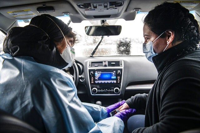 In this Thursday, April 16, 2020, photograph, nurse practitioner Lisa Robbiano, left, talks to Fabiola Grajales while checking her lungs and heart rate in Robbiano's car next to the MIRA COVID-19 testing bus in El Jebel, Colo. This was Grajales's fourth COVID-19 test to tell her whether she was finally free of the coronavirus and able to be near her family again.   (Kelsey Brunner/The Aspen Times via AP)