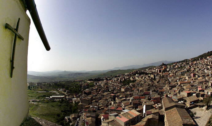 """FILE -- In this file photo taken on April 24, 2006, a crucifix towers over Corleone, Italy.The Sicilian town of Corleone, made famous by the fictional Mafia clan in """"The Godfather,"""" has ordered schools closed and a limited lockdown after a spate of coronavirus infections were tied to a big wedding there last week. (AP Photo/Gregorio Borgia)"""