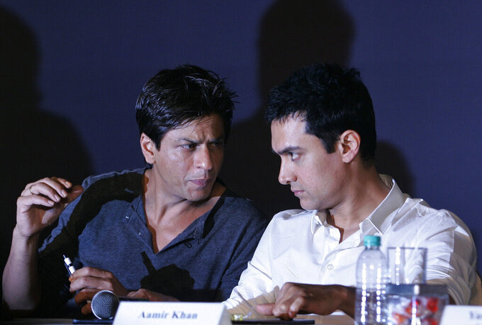 """FILE- In this April 7, 2009, file photo, Bollywood actors Shah Rukh Khan, left, and Aamir Khan speak during a press conference in Mumbai, India. Top Bollywood filmmakers, including superstar actors Aamir Khan and Shah Rukh Khan, have on Monday, Oct. 12, 2020, filed a lawsuit against television news channels Republic TV and Times Now following the suspected suicide of actor Sushant Singh Rajput that set off a media frenzy and gripped the nation. Claiming that Rajput had been murdered, many television channels held filmmakers who had allegedly rejected him for roles responsible for his suicide and accused many Bollywood celebrities of being part of a """"drug cartel,"""" even though the police have maintained that there was no foul play. (AP Photo/Rajanish Kakade, File)"""