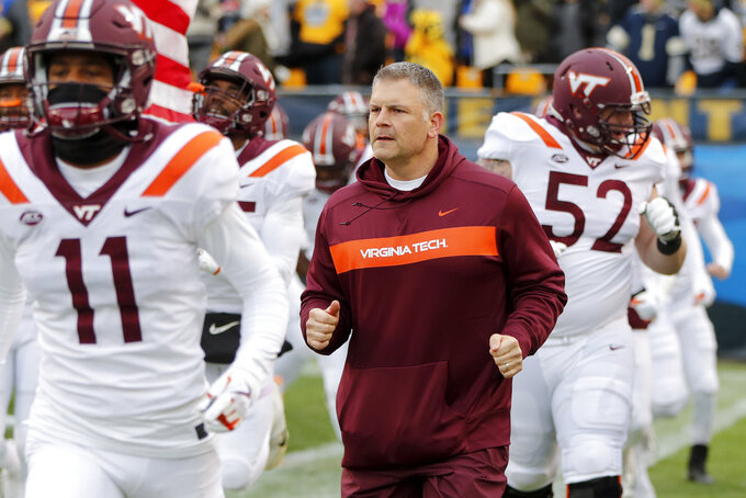 FILE - In this Saturday, Nov. 10, 2018, file photo, Virginia Tech head coach Justin Fuente, center, takes the field with his team before an NCAA college football game against Virginia Tech, in Pittsburgh. Hurricane Florence and the looming bowl season has South Carolina and Virginia Tech closing their football seasons against teams that were never on their schedule. (AP Photo/Keith Srakocic, File)