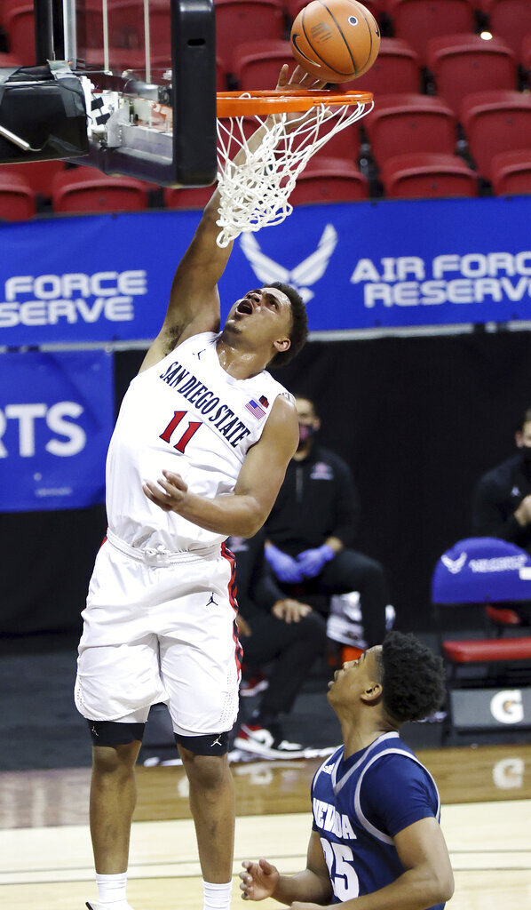 San Diego State forward Matt Mitchell (11) shoots as Nevada guard Grant Sherfield (25) defends during the second half of an NCAA college basketball game in the semifinals of the Mountain West Conference men's tournament Friday, March 12, 2021, in Las Vegas. (AP Photo/Isaac Brekken)