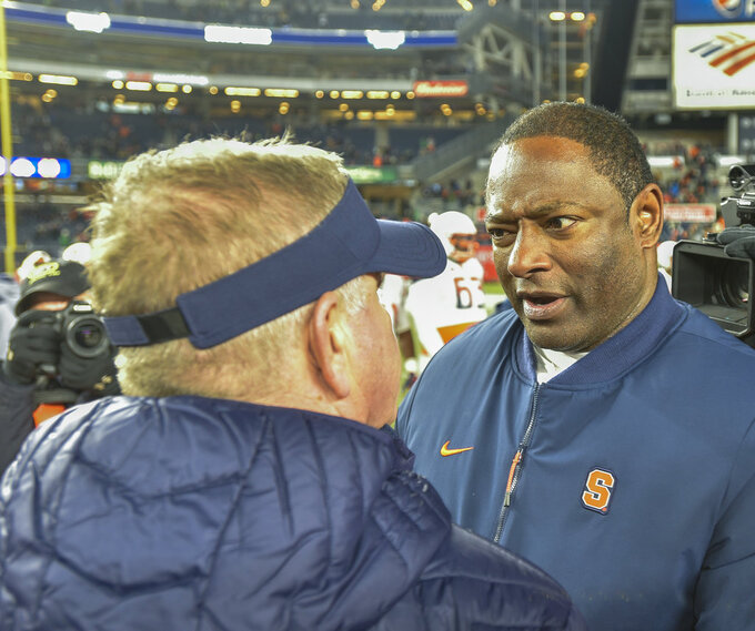 Syracuse head coach Dino Babers, right, greets Notre Dame head coach Brian Kelly after an NCAA college football game, Saturday, Nov. 17, 2018, at Yankee Stadium in New York. (AP Photo/Howard Simmons)
