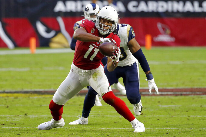 Arizona Cardinals wide receiver Larry Fitzgerald (11) makes a catch as Los Angeles Rams linebacker Travin Howard pursues during the second half of an NFL football game, Sunday, Dec. 1, 2019, in Glendale, Ariz. (AP Photo/Rick Scuteri)