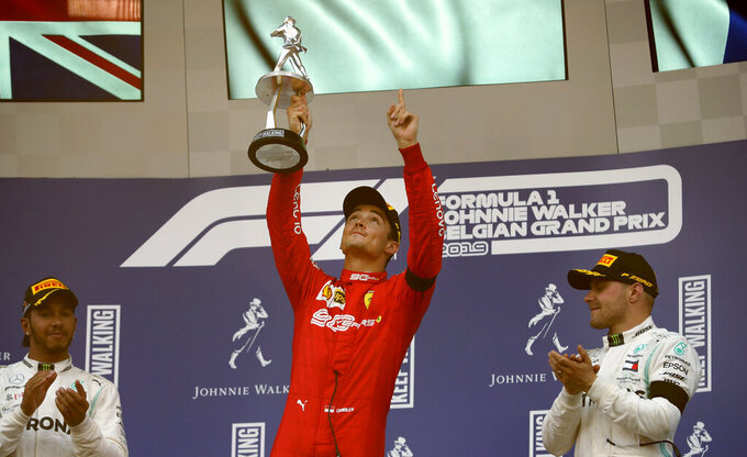 Ferrari driver Charles Leclerc of Monaco, center, lifts the trophy after finishing first in the Belgian Formula One Grand Prix in Spa-Francorchamps, Belgium, Sunday, Sept. 1, 2019. Mercedes driver Lewis Hamilton of Britain, left, placed second and Mercedes driver Valtteri Bottas of Finland, right, placed third. (AP Photo/Francisco Seco)