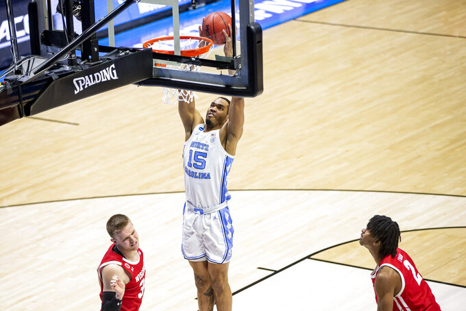 North Carolina's Garrison Brooks (15) dunks over Wisconsin's Brad Davison, left, and Aleem Ford (2) during the second half of a first-round game in the NCAA men's college basketball tournament, Friday, March 19, 2021, at Mackey Arena in West Lafayette, Ind. (AP Photo/Robert Franklin)