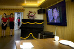 FILE - In this Wednesday, Aug. 15, 2018 photo, waitresses stand near a television screen showing a period drama in Pyongyang, North Korea. North Korean pop culture, long dismissed by critics as a kitschy throwback to the dark days of Stalinism, is getting a major upgrade under leader Kim Jong Un. The changes are being seen in everything from television dramas and animation programs to the variety and packaging of consumer goods, which have improved significantly under Kim. (AP Photo/Ng Han Guan, File)