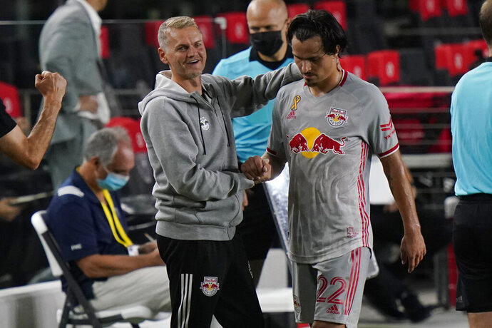 New York Red Bulls interim head coach Bradley Carnell, left, greets midfielder Florian Valot, right, as he comes off the field during the second half of an MLS soccer match against Inter Miami, Wednesday, Sept. 23, 2020, in Fort Lauderdale, Fla. (AP Photo/Lynne Sladky)
