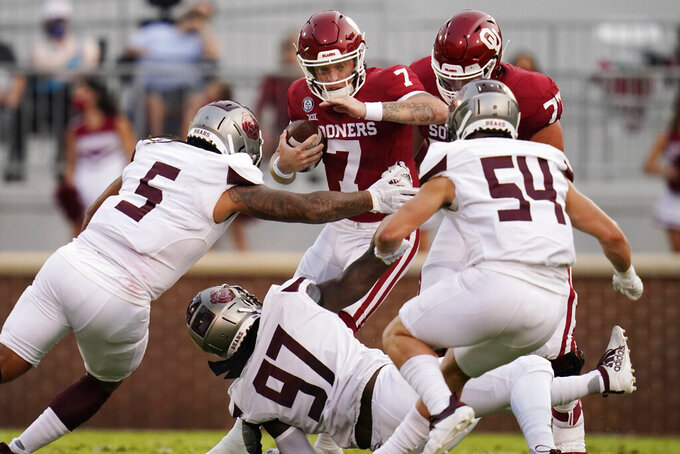 Oklahoma quarterback Spencer Rattler (7) carries against Missouri State defenders Ferrin Manulelua (5), Michael Pope (97), and Von Young (54) in the first half of an NCAA college football game Saturday, Sept. 12, 2020, in Norman, Okla. (AP Photo/Sue Ogrocki, Pool)