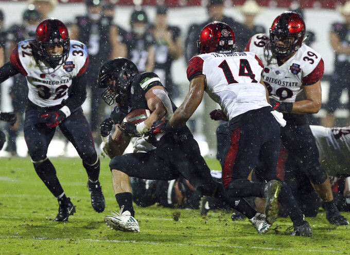 Ohio running back A.J. Ouellette (45) tries to evade a tackle by San Diego State safety Tariq Thompson (14) in the second half of the Frisco Bowl NCAA college football game, Wednesday, Dec. 19, 2018, in Frisco, Texas. (AP Photo/Richard W. Rodriguez)