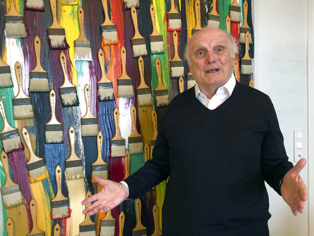 In this photo taken on Monday, March 2, 2020, billionaire art dealer David Nahmad poses in front of a colorful work by French-born American artist Arman, in Nahmad's home in Monaco. Nahmad has spent decades accumulating what he believes is now the world's largest private collection of works by Pablo Picasso, but he is about to part with one of them. A still life that Picasso painted in 1921 is being raffled off for charity in Paris this month with tickets at 100 euros each. (AP Photo/John Leicester)