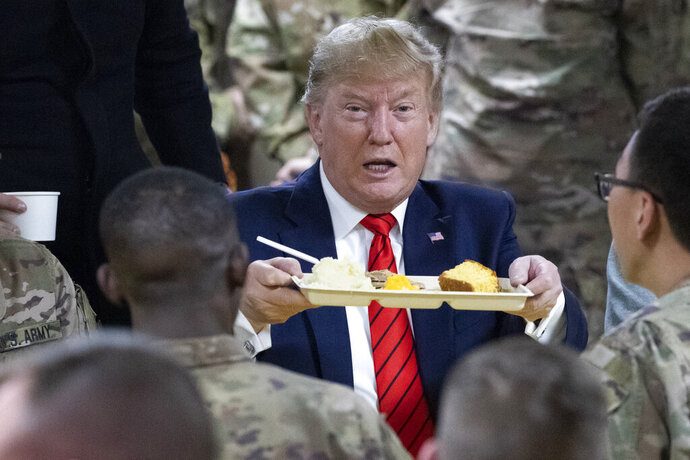 President Donald Trump holds up a tray of Thanksgiving dinner during a surprise Thanksgiving Day visit to the troops, Thursday, Nov. 28, 2019, at Bagram Air Field, Afghanistan. (AP Photo/Alex Brandon)