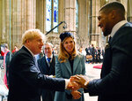 FILE - In this Monday March 9, 2020 file photo Britain's Prime Minister Boris Johnson and his fiancee partner Carrie Symonds talk with British boxer Anthony Joshua, right, as they leave after attending the annual Commonwealth Service at Westminster Abbey in London. British Prime Minister Boris Johnson has tested positive for the new coronavirus. Johnson's office said Friday March 27, 2020 that he was tested after showing mild symptoms, Downing St. says Johnson is self-isolating and continuing to lead the country's response to COVID-19. (Ben Stansall / Pool via AP, File)