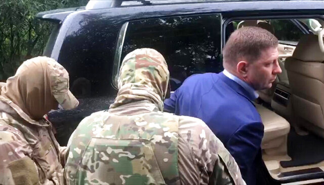 In this image distributed by Russian Investigative Committee, Sergei Furgal, the governor of the Khabarovsk region is escorted by Russian Federal Security Service (FSB, Soviet KGB successor) and Russian Investigative Committee agents in Khabarovsk, Russia, Thursday, July 9, 2020. Sergei Furgal, the governor of the Khabarovsk region along the border with China, was arrested in Khabarovsk and was flown to Moscow and has been arrested on charges of involvement in multiple murders. (The Investigative Committee of the Russian Federation via AP)