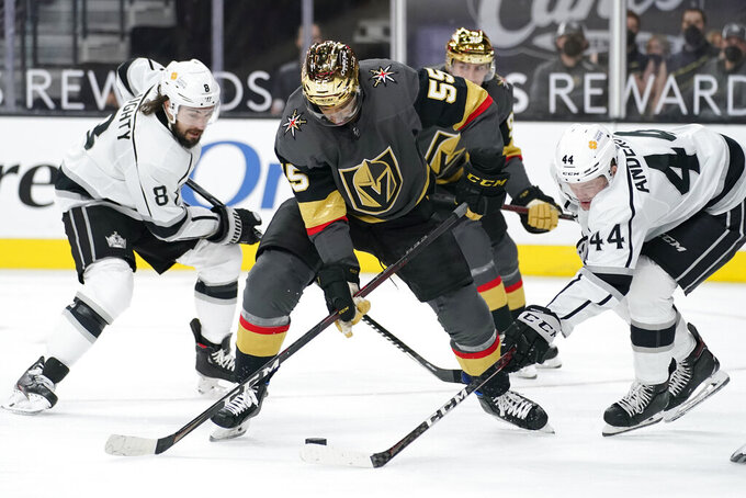 Vegas Golden Knights right wing Keegan Kolesar (55) vies for the puck with Los Angeles Kings defenseman Mikey Anderson (44) and defenseman Drew Doughty (8) during the second period of an NHL hockey game Monday, March 29, 2021, in Las Vegas. (AP Photo/John Locher)