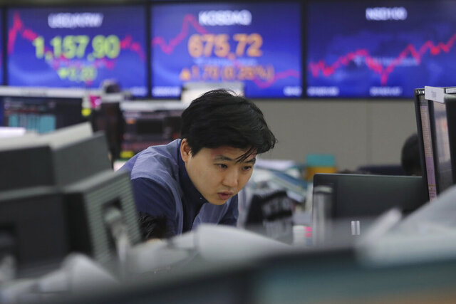A currency trader watches monitors at the foreign exchange dealing room of the KEB Hana Bank headquarters in Seoul, South Korea, Friday, Jan. 3, 2020. Asian stocks were mixed Friday and oil prices surged after an Iranian general was killed by U.S. forces in Iraq. (AP Photo/Ahn Young-joon)