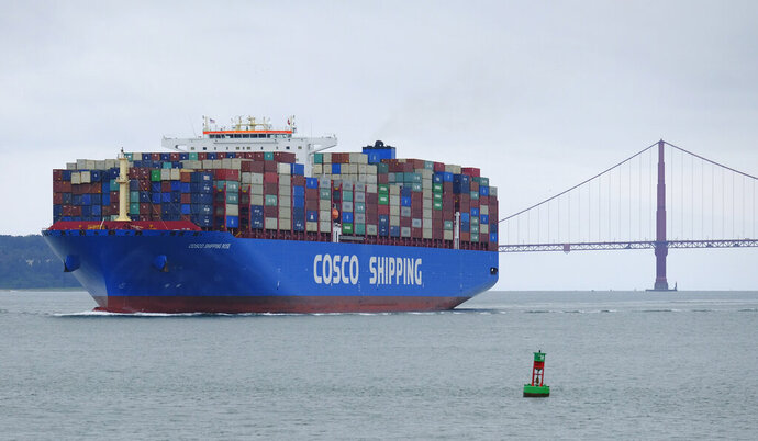 FILE - In this May 14, 2019 file photo, a Cosco Shipping container ship passes the Golden Gate Bridge in San Francisco bound for the Port of Oakland. For major shipping companies dealing with trade wars and a slowing global growth, conditions appear to have deteriorated as 2019 came to a close.  Global shipping and logistics provider Expeditors International said Friday, Jan. 17, 2020 that it expects fourth quarter operating income to fall between $177 million and $183 million.  (AP Photo/Eric Risberg, File)