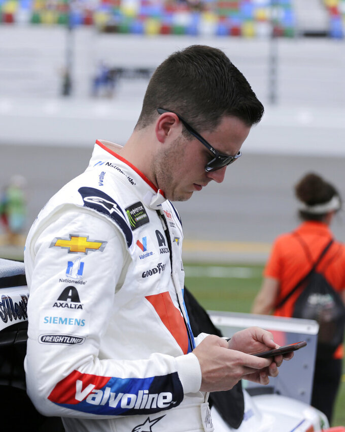 Alex Bowman checks his cell phone on pit road before a NASCAR auto race at Daytona International Speedway on Sunday, July 7, 2019, in Daytona Beach, Fla. (AP Photo/Terry Renna)