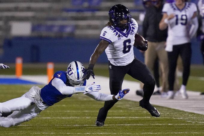 TCU running back Zach Evans (6) gets past Kansas cornerback Elijah Jones (4) during the first half of an NCAA college football game in Lawrence, Kan., Saturday, Nov. 28, 2020. (AP Photo/Orlin Wagner)