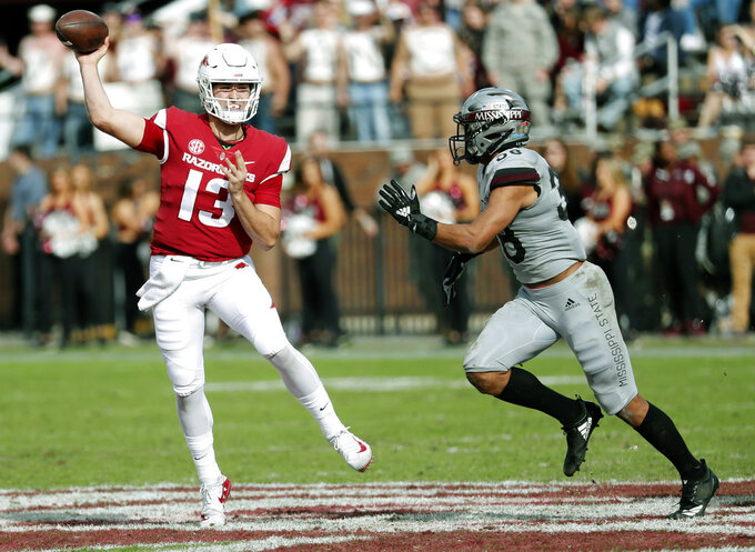 Arkansas quarterback Connor Noland (13) passes as he is being rushed by Mississippi State safety Johnathan Abram (38) during the second half of an NCAA college football game in Starkville, Miss., Saturday, Nov. 17, 2018. Mississippi State won 52-6. (AP Photo/Rogelio V. Solis)