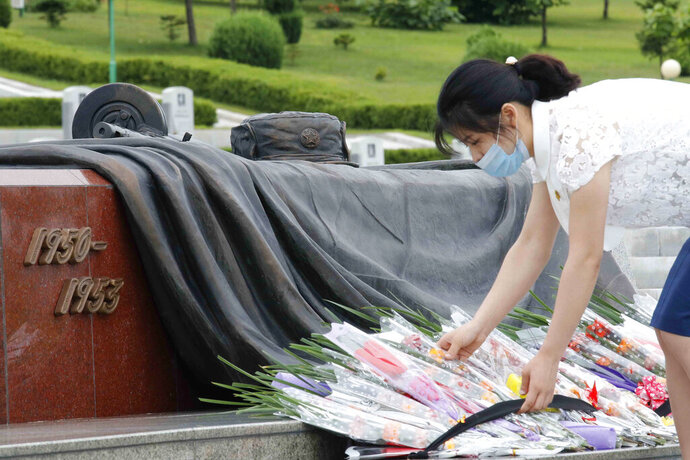 A North Korean woman lays a bouquet of flowers during a visit to the Fatherland Liberation War Martyrs Cemetery to pay respects to the monument to the fallen soldiers of the Korean People's Army in Pyongyang, North Korea, Thursday, June 25, 2020. North and South Korea on Thursday marked the 70th anniversary of the start of the Korean War with largely subdued commemorations amid the coronavirus pandemic, a day after the North abruptly halted a pressure campaign against the South. (AP Photo/Jon Chol Jin)