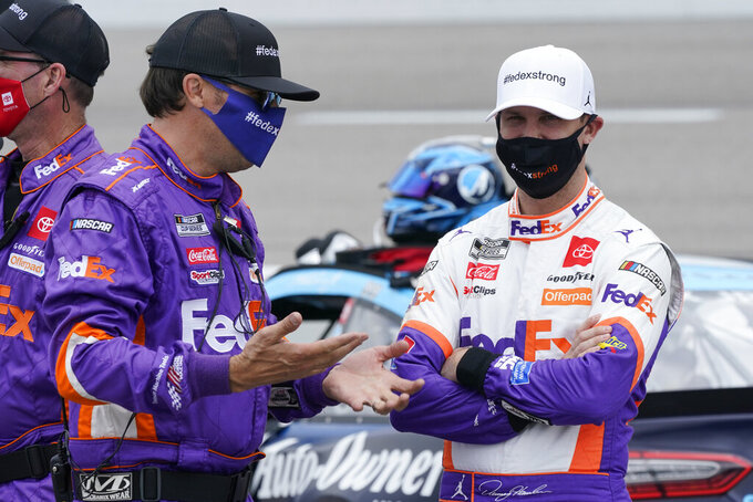 Denny Hamlin, right, talks to a crew member prior to the start of the NASCAR Cup Series auto race at Richmond International Raceway in Richmond, Va., Sunday, April 18, 2021. (AP Photo/Steve Helber)