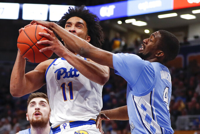 Pittsburgh's Justin Champagnie (11) shoots as North Carolina's Brandon Robinson (4) defends during the first half of an NCAA college basketball game, Saturday, Jan. 18, 2020, in Pittsburgh. (AP Photo/Keith Srakocic)
