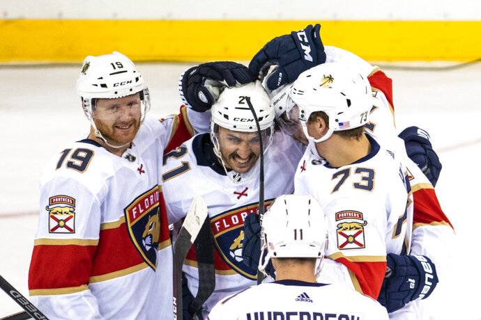 Florida Panthers defenseman Mike Matheson (19) and left wing Dryden Hunt (73) celebrate with center Vincent Trocheck (21) after he scored during the shootout in the team's NHL hockey game against the New York Rangers, Sunday, Nov. 10, 2019, in New York. (AP Photo/Corey Sipkin)