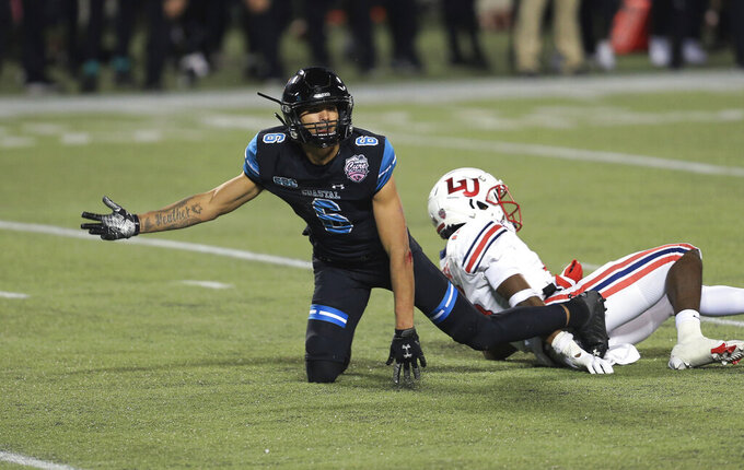 Coastal Carolina wide receiver Jaivon Heiligh (6) reacts after an incomplete pass defended by Liberty cornerback Quinton Reese (16) on the final drive during overtime of the Cure Bowl NCAA college football game Saturday, Dec. 26, 2020, in Orlando, Fla. Liberty won after blocking a field goal attempt. (AP Photo/Matt Stamey)