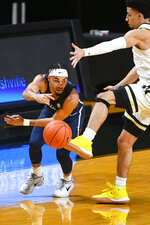 Richmond guard Jacob Gilyard, left, passes as Vanderbilt guard Scotty Pippen Jr. defends during the first half of an NCAA college basketball game Wednesday, Dec. 16, 2020, in Nashville. (AP Photo/John Amis)