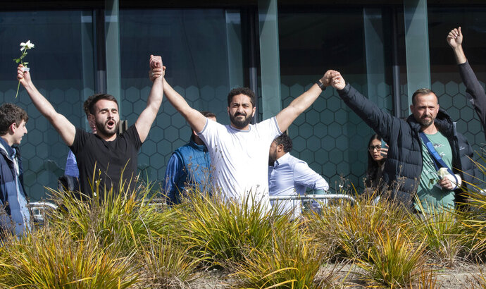 Mosque shooting survivors from left, Mustafa Boztas, Wassail Daragmih and Temel Atacocugu celebrate as they leave the Christchurch High Court after the sentencing hearing for Australian Brenton Harrison Tarrant, in Christchurch, New Zealand, Thursday, Aug. 27, 2020. Tarrant, a white supremacist who killed 51 worshippers at two New Zealand mosques in March 2019 was sentenced to life in prison without the possibility of parole. (AP Photo/Mark Baker)