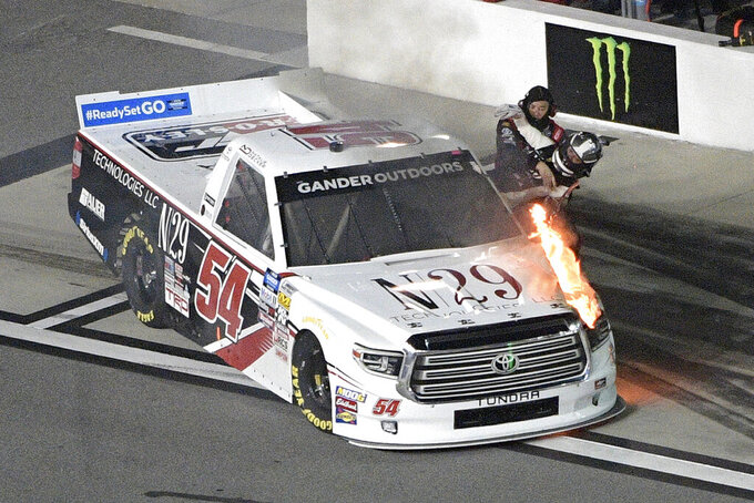 Natalie Decker (54) is helped out of her truck on pit road after it caught fire on the track during a NASCAR Truck Series race at Daytona International Speedway Friday, Feb. 15, 2019, in Daytona Beach, Fla. (AP Photo/Phelan M. Ebenhack)