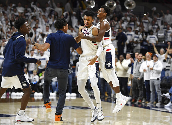 Connecticut's Tyler Polley, second from right, is congratulated by teammates Christian Vital, right, Temi Aiyegbusi, left, and James Bouknight during the second half of an NCAA college basketball game against Florida, Sunday, Nov. 17, 2019, in Storrs, Conn. (AP Photo/Jessica Hill)