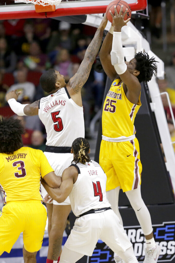 Louisville's Malik Williams (5) fouls Minnesota's Daniel Oturu (25) during the first half of a first round men's college basketball game in the NCAA Tournament, in Des Moines, Iowa, Thursday, March 21, 2019. (AP Photo/Nati Harnik)
