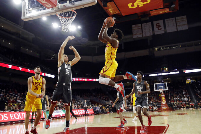 Southern California 's Ethan Anderson catches a high pass and scores during the first half of the team's NCAA college basketball game against Washington State on Saturday, Feb. 15, 2020, in Los Angeles. (AP Photo/Marcio Jose Sanchez)