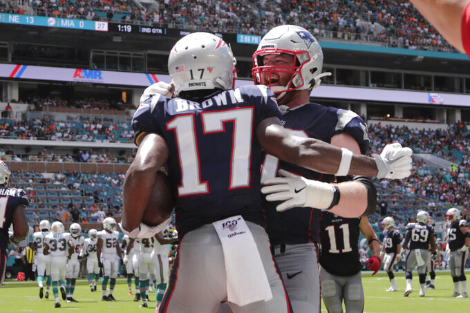 New England Patriots offensive guard Joe Thuney (62) congratulates wide receiver Antonio Brown (17) after Brown scored a touchdown, during the first half at an NFL football game against the Miami Dolphins, Sunday, Sept. 15, 2019, in Miami Gardens, Fla. (AP Photo/Lynne Sladky)