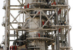 In this photo opportunity during a trip organized by Saudi information ministry, workers fix the damage in the Aramco's Khurais oil field, Saudi Arabia, Friday, Sept. 20, 2019, after it was hit during Sept. 14 attack. Saudi officials brought journalists Friday to see the damage done in an attack the U.S. alleges Iran carried out. (AP Photo/Amr Nabil)