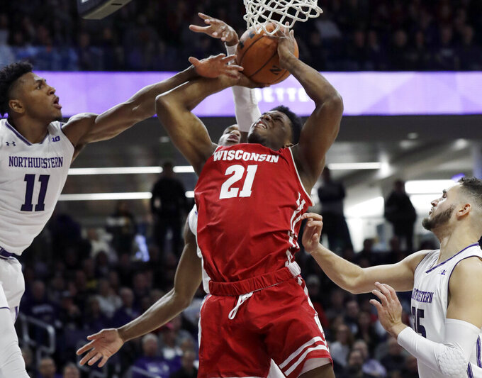 Wisconsin guard Khalil Iverson (21) shoots against Northwestern guard Anthony Gaines, left, forward Aaron Falzon, right, and forward Vic Law during the first half of an NCAA college basketball game Saturday, Feb. 23, 2019, in Evanston, Ill. (AP Photo/Nam Y. Huh)