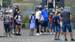 Parents wait with children on the schoolyard for the start of their first day at a school in Gelsenkirchen, Germany, Wednesday, Aug. 12, 2020. Students in North Rhine-Westphalia will have to wear face masks at all times due to the coronavirus pandemic as they return to school this Wednesday. (AP Photo/Martin Meissner)