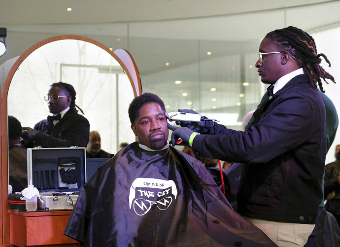 In this Sunday, Feb. 17, 2019 photo, Yusuf Lateef receives a haircut from Andre